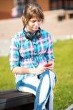 Estudiante universitaria joven sonriente que manda un SMS en un teléfono celular Imagen de archivo libre de regalías