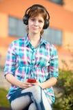 Estudiante universitaria joven sonriente que manda un SMS en un teléfono celular Fotos de archivo