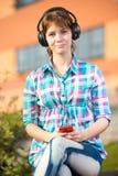 Estudiante universitaria joven sonriente que manda un SMS en un teléfono celular campus Fotos de archivo