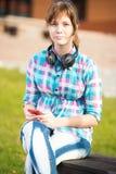 Estudiante universitaria joven sonriente que manda un SMS en un teléfono celular campus Foto de archivo libre de regalías