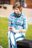 Estudiante universitaria joven sonriente que manda un SMS en un teléfono celular campus Fotos de archivo libres de regalías
