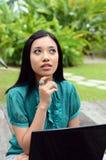 Estudiante universitaria musulmán bastante asiática de los jóvenes del retrato con el ordenador portátil Imagen de archivo libre de regalías
