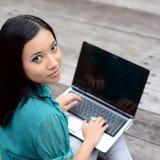 Estudiante universitaria musulmán bastante asiática de los jóvenes del retrato con el ordenador portátil y la sonrisa Fotografía de archivo