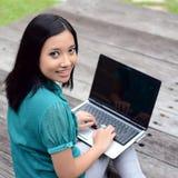 Estudiante universitaria musulmán bastante asiática de los jóvenes del retrato con el ordenador portátil y la sonrisa Foto de archivo libre de regalías