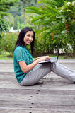 Estudiante universitaria musulmán bastante asiática de los jóvenes del retrato con el ordenador portátil y la sonrisa Imagen de archivo libre de regalías