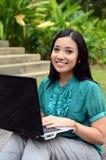 Estudiante universitaria musulmán bastante asiática de los jóvenes del retrato con el ordenador portátil y la sonrisa Imagen de archivo
