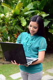 Estudiante universitaria musulmán bastante asiática de los jóvenes del retrato con el ordenador portátil y la sonrisa Fotografía de archivo libre de regalías