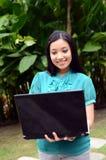 Estudiante universitaria musulmán bastante asiática de los jóvenes del retrato con el ordenador portátil y la sonrisa Imágenes de archivo libres de regalías