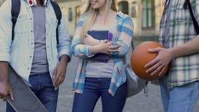 Estudiante universitaria popular que se coloca entre dos individuos, eligiendo la fecha, afecto almacen de video