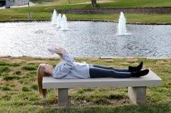 Estudiante universitaria que estudia por el lago Imagen de archivo libre de regalías