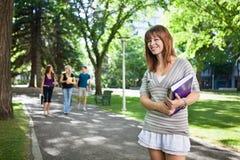 Estudiante universitaria que se coloca con un libro Fotografía de archivo libre de regalías