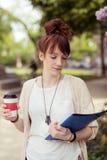 Estudiante universitaria que sostiene un café mientras que lee un libro Fotografía de archivo libre de regalías