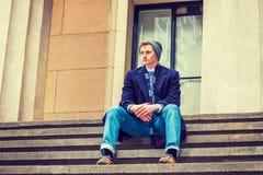 Estudiante universitario adolescente americano que se sienta en las escaleras afuera en los wi Imagenes de archivo