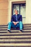 Estudiante universitario adolescente americano que se sienta en las escaleras afuera en los wi Foto de archivo