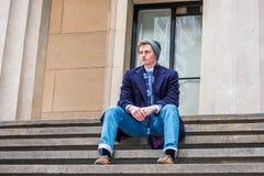 Estudiante universitario adolescente americano que se sienta en las escaleras afuera en los wi Fotos de archivo