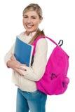 Estudiante universitario alegre que presenta con la mochila rosada Fotos de archivo