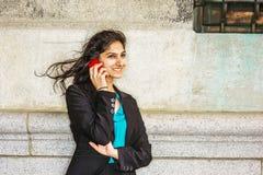 Estudiante universitario americano del indio que invita a outsi del teléfono celular Foto de archivo libre de regalías