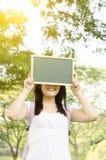 Estudiante universitario asiático con la pizarra en blanco Imagen de archivo