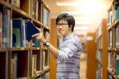 Estudiante universitario asiático joven del hombre que elige el libro en biblioteca Imagenes de archivo