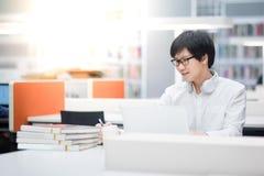 Estudiante universitario asiático joven del hombre que trabaja en biblioteca Imagenes de archivo