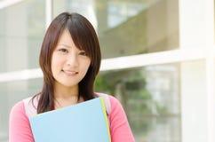 Estudiante universitario asiático joven en el campus de la escuela Imagen de archivo libre de regalías