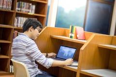 Estudiante universitario asiático joven que usa el ordenador portátil en biblioteca Imagenes de archivo