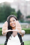 Estudiante universitario asiático que hace un marco Imagenes de archivo