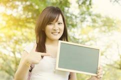 Estudiante universitario asiático que muestra la pizarra en blanco Imagen de archivo