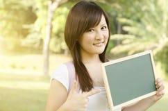Estudiante universitario asiático que señala en la pizarra en blanco Imagenes de archivo