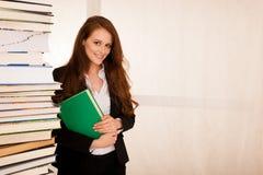 Estudiante universitario atractivo con una pila de libros Foto de archivo