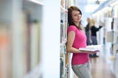 Estudiante universitario bastante joven en una biblioteca Fotos de archivo libres de regalías