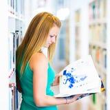Estudiante universitario bastante joven en una biblioteca Imagen de archivo libre de regalías