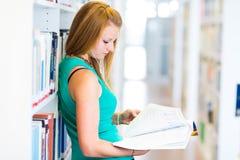 Estudiante universitario bastante joven en una biblioteca Imágenes de archivo libres de regalías