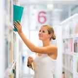 Estudiante universitario bastante joven en una biblioteca Imagen de archivo