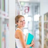 Estudiante universitario bastante joven en una biblioteca Fotografía de archivo libre de regalías