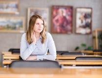 Estudiante universitario bastante joven en una biblioteca Mirada lejos Imagenes de archivo