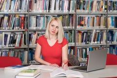 Estudiante universitario bonito en una biblioteca Imágenes de archivo libres de regalías