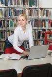 Estudiante universitario bonito en una biblioteca Imagen de archivo libre de regalías
