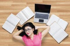 Estudiante universitario bonito que se relaja en el piso Imagen de archivo