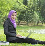 Estudiante universitario bonito que trabaja en su ordenador portátil mientras que descansa en el parque Foto de archivo
