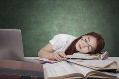 Estudiante universitario cansado que duerme en el escritorio en clase Imagen de archivo
