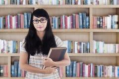 Estudiante universitario con el pelo largo en biblioteca Fotos de archivo libres de regalías