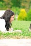 Estudiante universitario con la computadora portátil en la hierba Foto de archivo