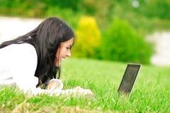 Estudiante universitario con la computadora portátil en la hierba Fotos de archivo libres de regalías