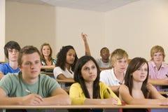 Estudiante universitario con la mano levantada en conferencia Foto de archivo libre de regalías