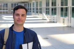 Estudiante universitario con la mochila y los libros que presentan - imagen común imagen de archivo libre de regalías