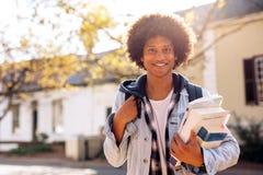 Estudiante universitario con las porciones de libros en campus de la universidad Imagenes de archivo