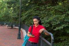 Estudiante universitario con una mochila que mira su teléfono celular Imágenes de archivo libres de regalías