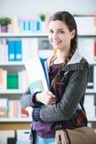Estudiante universitario confiado en la biblioteca Imagen de archivo libre de regalías