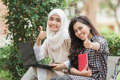 Estudiante universitario de dos asiáticos que usa el ordenador portátil Foto de archivo libre de regalías